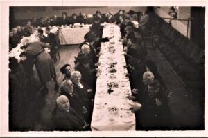 Photo in B+W of formal dinner and diners at long tables, undated.