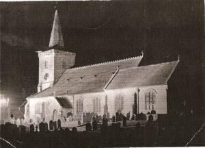 Photo of Brading Church floodlit at night.